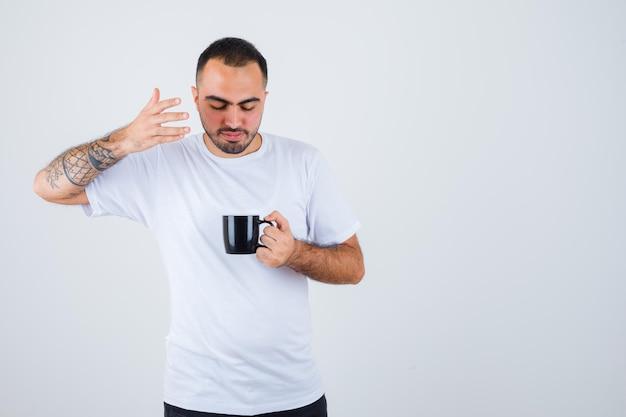 お茶を持って、白いtシャツと黒いズボンでそれに向かって手を伸ばして集中して見える若い男