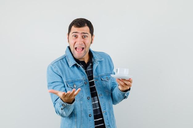 Молодой человек держит чашку чая в вопросительном жесте в футболке, куртке и выглядит взволнованным.