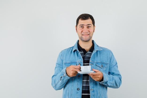 Молодой человек держит чашку чая в футболке, куртке и выглядит веселым.
