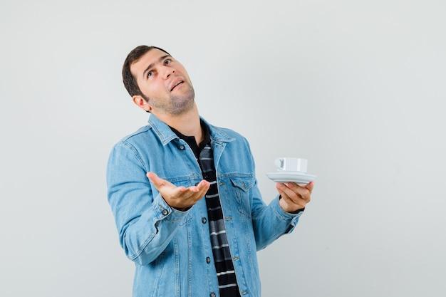 Молодой человек держит чашку чая в футболке, куртке и выглядит смущенным