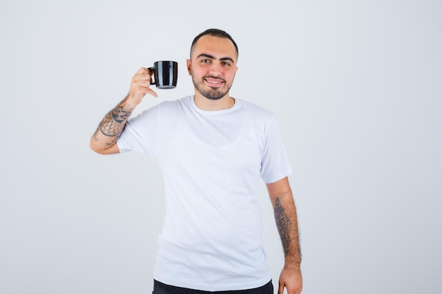 Молодой человек держит чашку чая в белой футболке и черных штанах и выглядит счастливым
