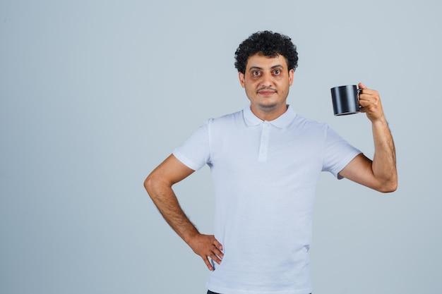 차 한 잔을 들고 흰색 티셔츠와 청바지를 입고 허리에 손을 대고 행복해 보이는 젊은 남자. 전면보기.