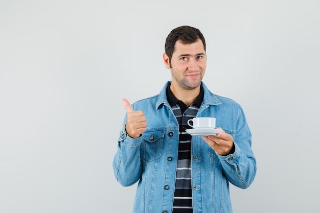 Молодой человек держит чашку чая, показывает большой палец вверх в футболке, куртке и выглядит довольным