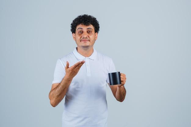 차 한 잔을 들고 흰색 티셔츠와 청바지를 입고 손을 뻗어 불쾌한 표정을 짓고 있는 젊은 남자.