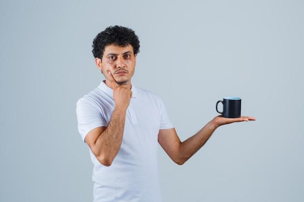 白いtシャツとジーンズで手に顎をもたれ、物思いにふける、正面図を見てお茶のカップを保持している若い男。