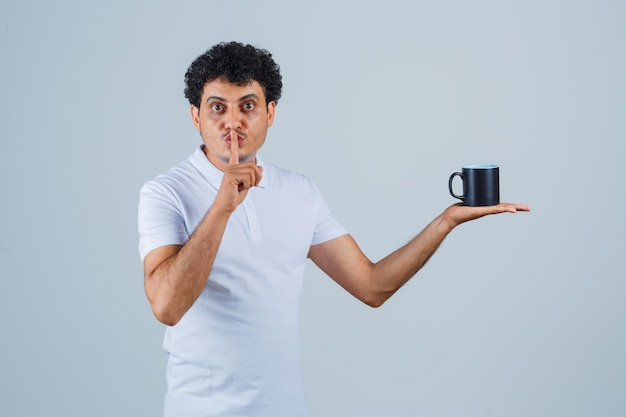 흰색 티셔츠와 청바지에 침묵 제스처를 보여주고 진지한 표정으로 차 한 잔을 들고 있는 젊은 남자. 전면보기.