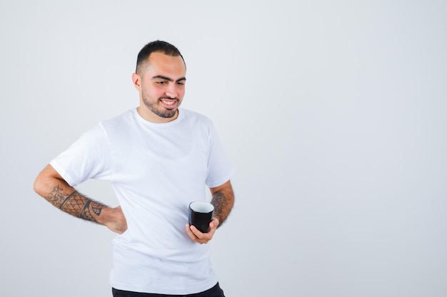 Young man holding cup of tea in one hand and holding hand on waist in white t-shirt and black pants and looking happy