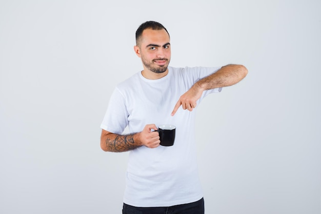 Young man holding cup of tea and pointing to it in white t-shirt and black pants and looking happy