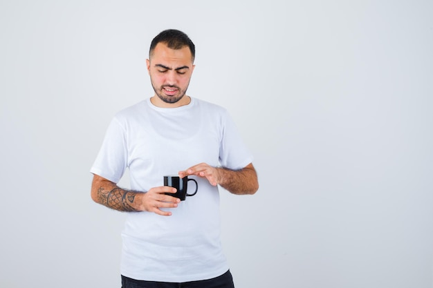 Young man holding cup of tea and putting hand on it in white t-shirt and black pants and looking focused