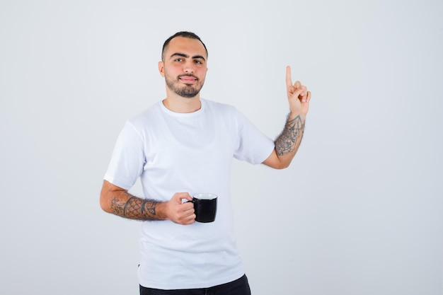 Young man holding cup of tea and raising index finger in eureka gesture in white t-shirt and black pants and looking happy
