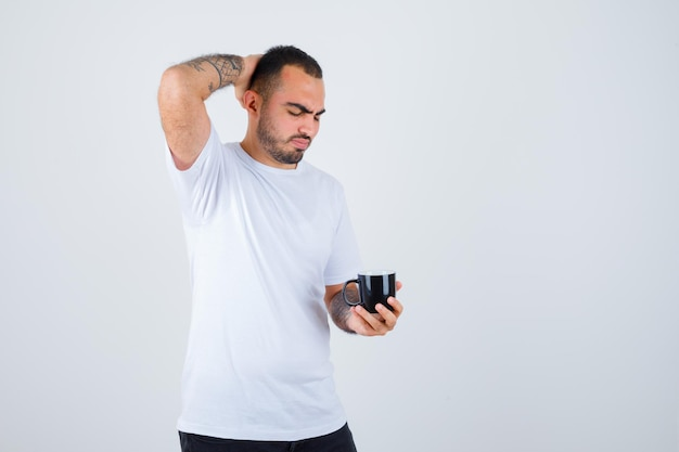 Young man holding cup of tea and scratching head in white t-shirt and black pants and looking serious