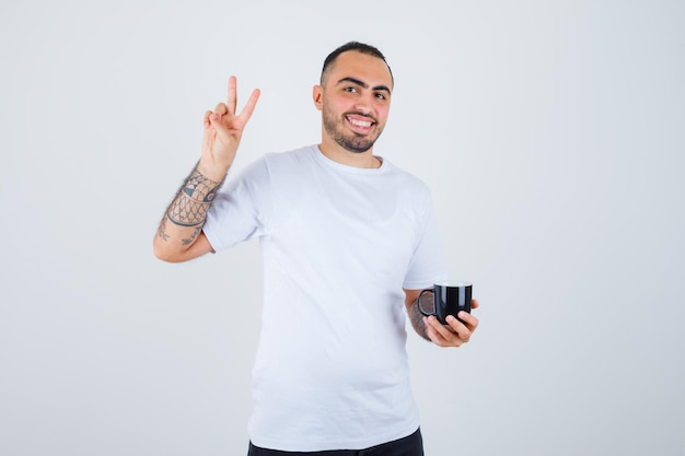 Young man holding cup of tea and showing peace sign in white t-shirt and black pants and looking happy
