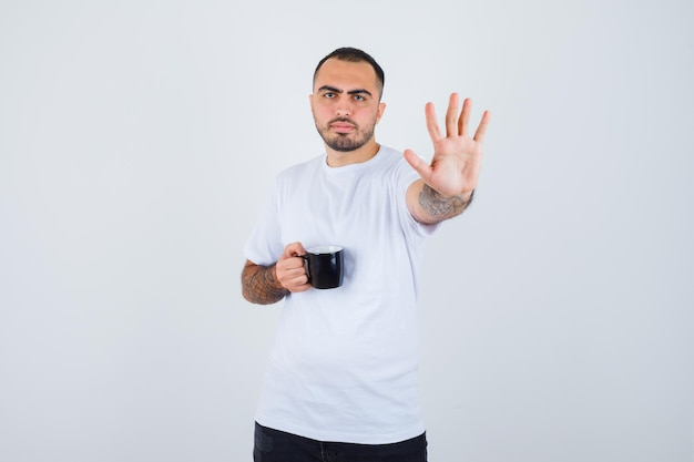 Young man holding cup of tea and showing stop in white t-shirt and black pants and looking serious