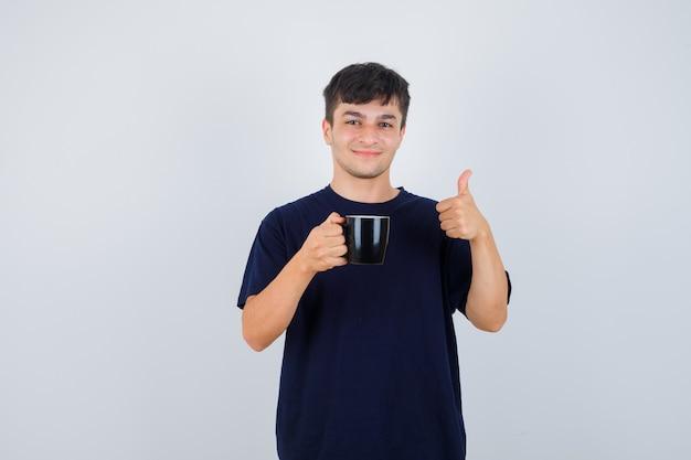 Giovane che tiene tazza di tè, mostrando il pollice in su in maglietta nera e guardando allegro. vista frontale.