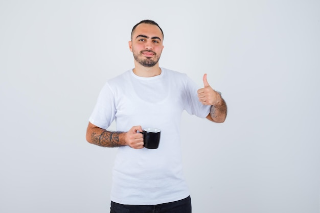 Young man holding cup of tea and showing thumb up in white t-shirt and black pants and looking happy