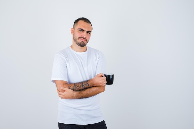 Young man holding cup of tea and standing arms crossed in white t-shirt and black pants and looking happy