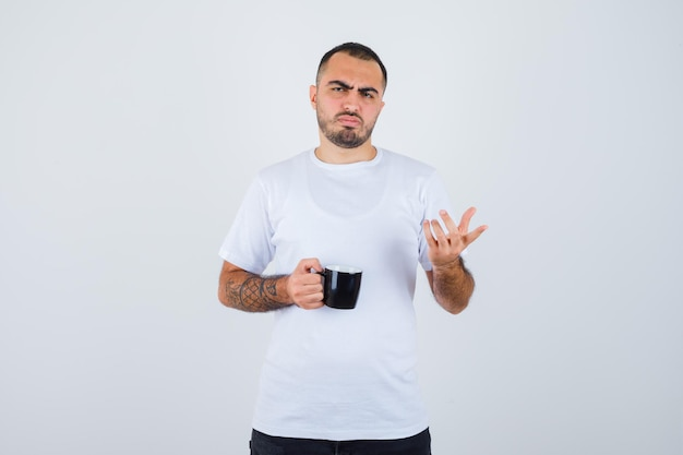 Young man holding cup of tea and stretching hand in questioning manner in white t-shirt and black pants and looking perplexed