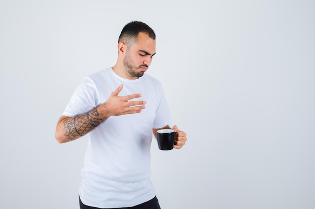 Young man holding cup of tea and stretching hand right in white t-shirt and black pants and looking focused