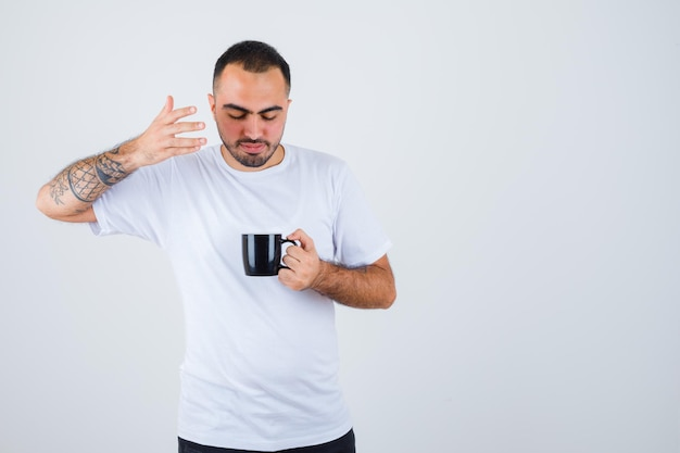 Young man holding cup of tea and stretching hand toward it in white t-shirt and black pants and looking focused