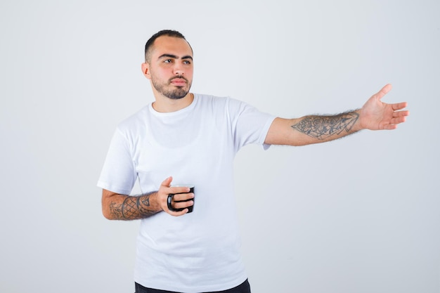 Young man holding cup of tea and stretching hand in white t-shirt and black pants and looking serious