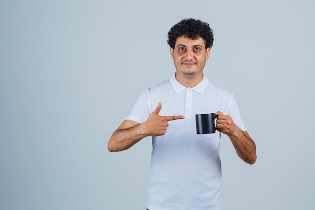 Giovane che tiene una tazza di tè mentre la indica in maglietta bianca e jeans e sembra felice. vista frontale.
