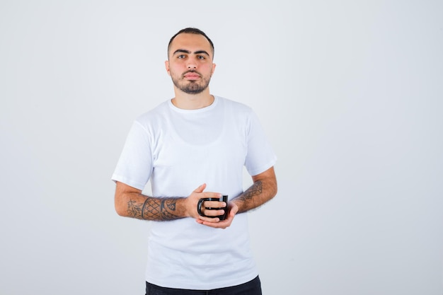 Young man holding cup of tea in white t-shirt and black pants and looking serious