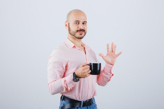 Young man holding cup while showing so-so gesture in pink shirt,jeans , front view.