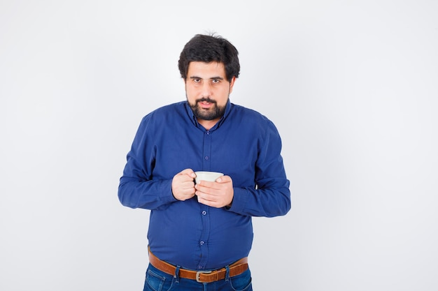 Young man holding cup with both hands in blue shirt and jeans and looking serious. front view.