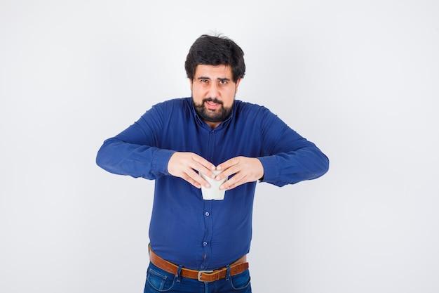 青いシャツとジーンズで両手でカップを保持し、楽観的な正面図を探している若い男。