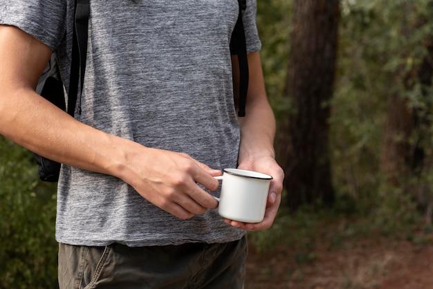 Молодой человек держит чашку
