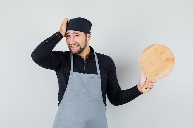 Young man holding cutting board while scratching head in shirt, apron and looking humble. front view.