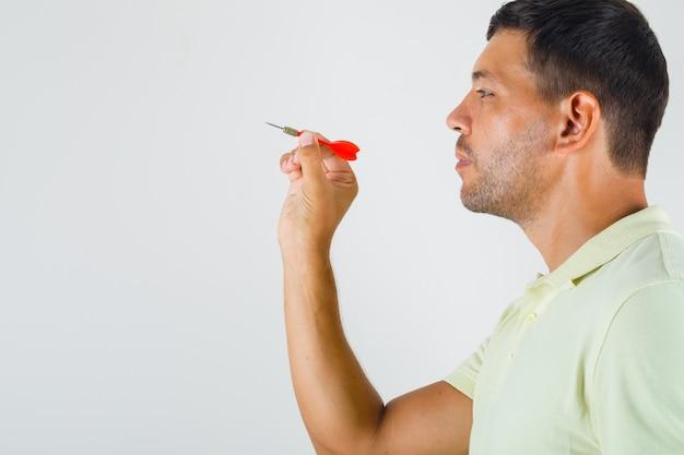 Young man holding dart arrow in t-shirt .