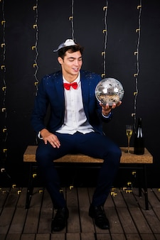 Young man holding disco ball on bench
