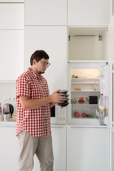 Молодой человек держит одноразовые пластиковые коробки с едой и кладет их в холодильник