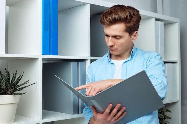 いくつかの重要な情報を見つけようとしているドキュメント ファイルを持っている若い男