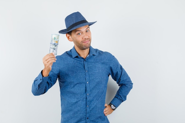 Young man holding dollar banknote in blue shirt, hat and looking merry. front view.