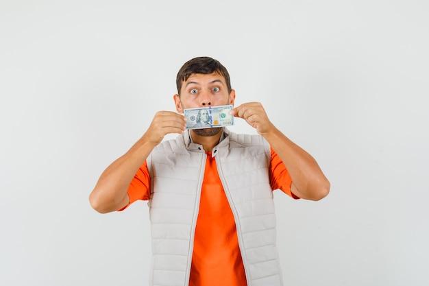 Giovane che tiene la fattura del dollaro sopra la bocca in maglietta, rivestimento e che sembra divertente. vista frontale.