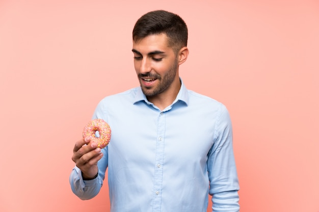 Young man holding a donut over isolated pink wall smiling a lot