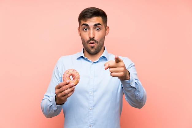 Young man holding a donut over isolated pink wall surprised and pointing front