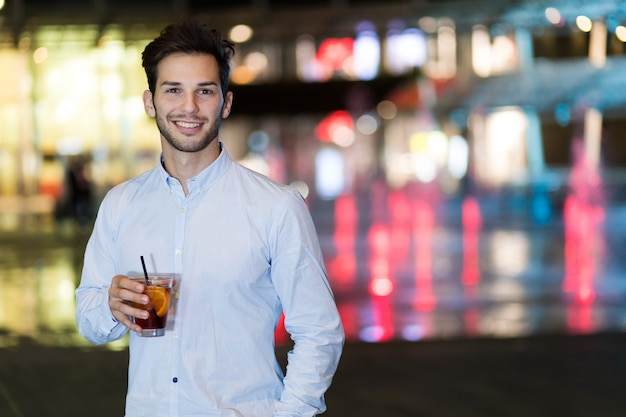 Young man holding a drink at a night club outdoor