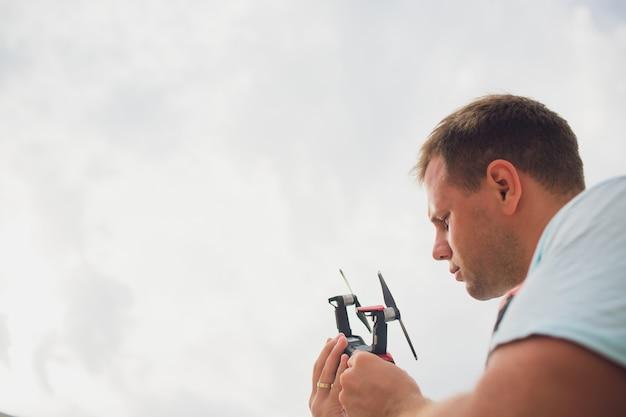 자연에서 비행 전에 무인 항공기를 들고 젊은 남자. 예쁜 남자는 야외 quadrocopter 조종사를 준비합니다. 프로펠러를 배치