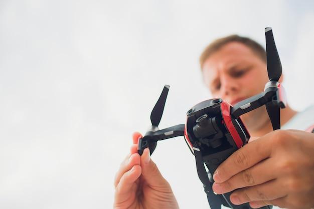 자연에서 비행 전에 무인 항공기를 들고 젊은 남자. 예쁜 남자는 야외 quadrocopter 조종사를 준비합니다.