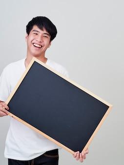 Young man holding empty blackboard