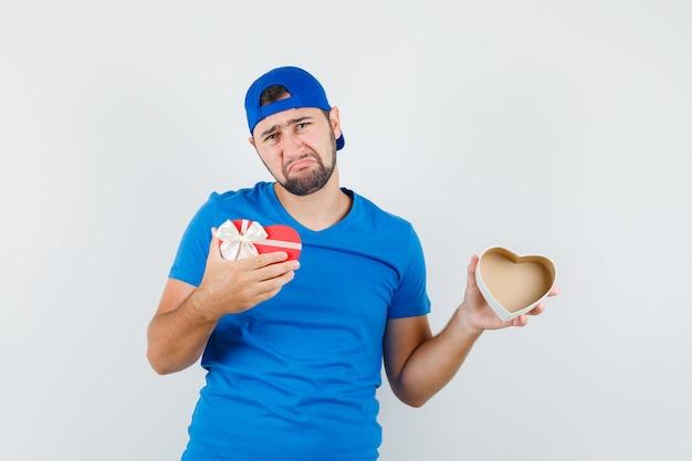 青いtシャツとキャップで空のギフトボックスを保持し、意気消沈している若い男