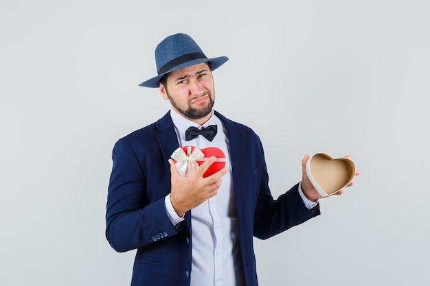 Young man holding empty present box in suit, hat and looking disappointed , front view.