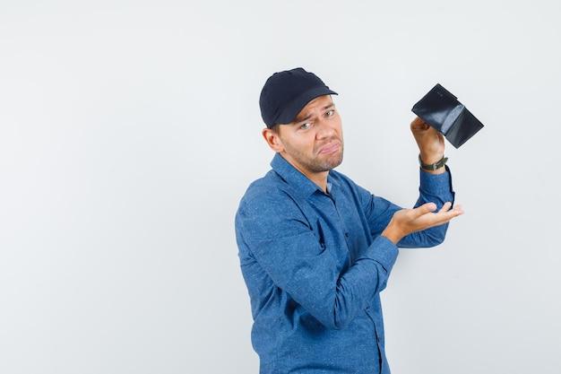 Молодой человек держит пустой бумажник в голубой рубашке, кепке и выглядит разочарованным, вид спереди.