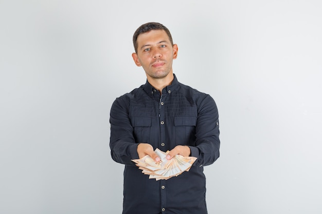 Молодой человек держит банкноты евро в черной рубашке