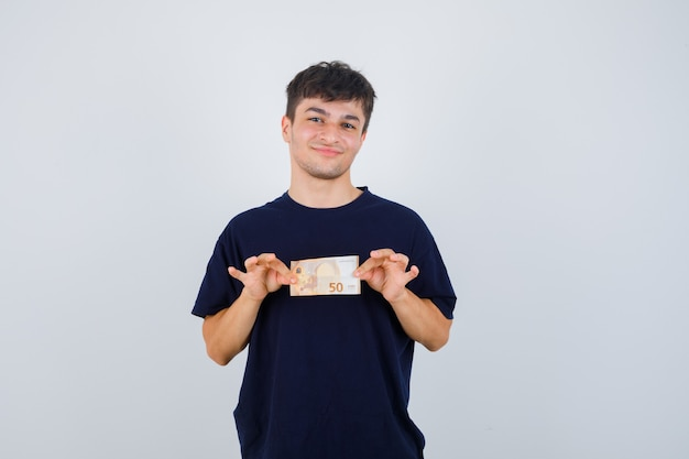 Young man holding euro bill in black t-shirt and looking confident. front view.