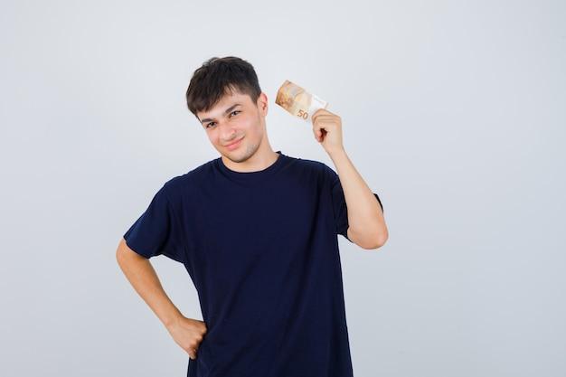 黒のtシャツでユーロ紙幣を保持し、自信を持って見える若い男。正面図。