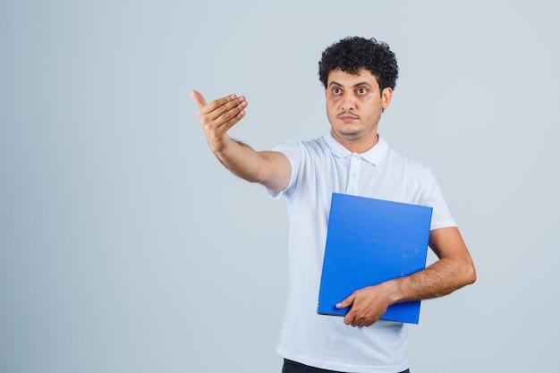 Молодой человек держит папку с файлами и приглашает прийти в белой футболке и джинсах и выглядит серьезным. передний план.
